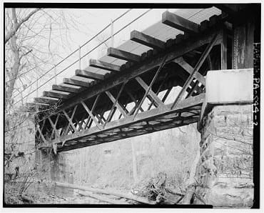A black and white image of an old railroad bridge with trusses under the deck.