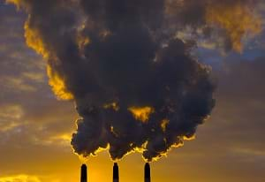 A photograph shows air pollution being released from three smokestacks.