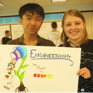"Two teens hold a poster they made that says, ""Engineering – the power to create."""