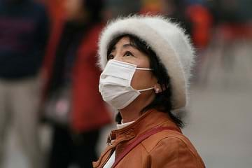 A photograph shows a woman wearing a white cloth mask over her moutn and nose to protect against air pollution in China.