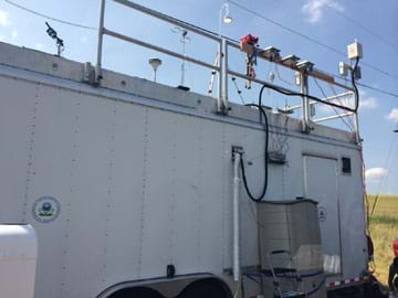 A photograph shows a white box-shaped trailer on wheels with railings around the rooftop onto which equipment is attached, including monitors, sensors, hoses and inlets into the trailer.