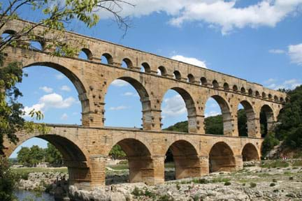 A photograph shows a three-layered, multi-arched Roman masonry aqueduct built across a river. Each level has different-sized arches.
