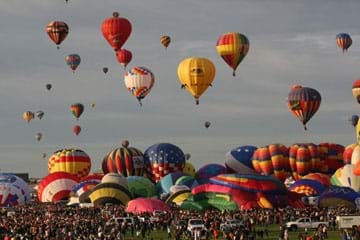 Photo shows a park filled with people and about 20 colorful hot air balloons on the ground. Another 22 hot air balloons are floating in the sky.