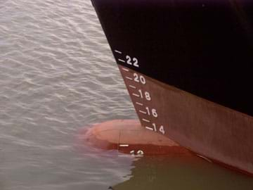 Photo shows a ship in water with numerical markings that indicate its displacement in the water.