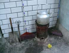 Photo shows a cylinder-shaped stove no wider than the teapot on top. No chimney. Shovels, tongs and brooms lie nearby.