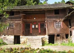 Photo shows the front view of a two-story wooden house raised on a stone foundation with a peaked tile roof, four windows and a centered double front door.