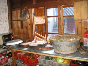 A waist-high kitchen counter against a wall holds cutting boards, knife and containers. Shelves below hold bins of fruits and vegetables. The wall is made of wooden boards with an operable two-part window.