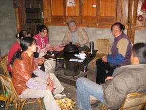 Photo shows six adults sitting around a coal stove inside a home.