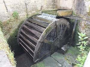 An overshot waterwheel showing water flowing through it in Goyet, Beligum.