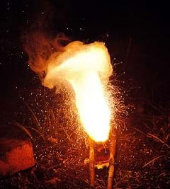 A photograph shows sparks flying off globules of molten iron, leaving smoke behind.