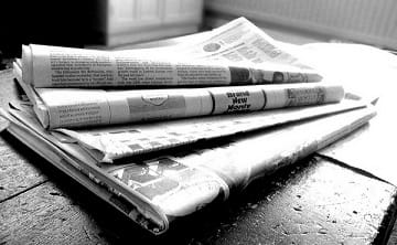 A stack of black and white newspapers.
