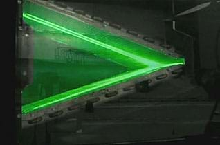 Photo shows a sheet of laser light illuminating the surfaces of a heat exchanger during an experiment.