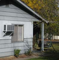 Photo shows the side of a house with a ventilated 2 x 3-foot box mounted to the exterior wall next to a window.