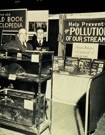 "A black/white photograph of two men standing in an exhibit booth with signs such as, ""Help Prevent the Pollution of Our Streams."""