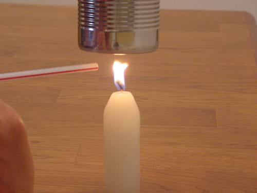 A photograph shows a candle burning below a soup can while someone uses a straw to gently blow the flame away from the bottom of the can, preventing the buildup of carbon.