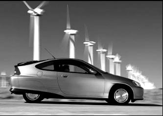Black and white, side view photograph of a silvery, small, modern-looking car with a row of spinning wind turbines in a line in the background.