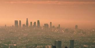 A photograph of a city skyline distorted and discolored due to smog.