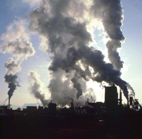 A photograph of industrial factories releasing pollutants. A grayish haze around the factory indicates the presence of industrial smog.