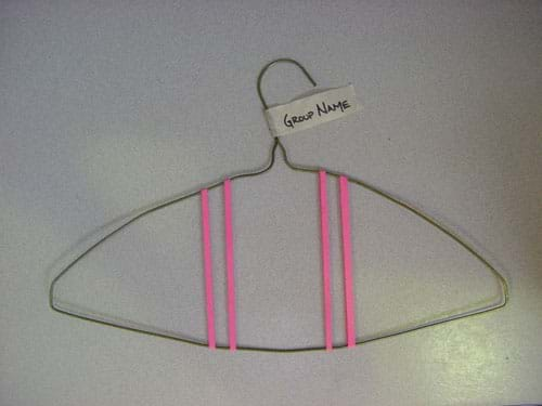 Photograph of a wire hanger with four rubber bands stretched across its top and bottom wires, with a masking tape tag on the hook, labeled with the group name.