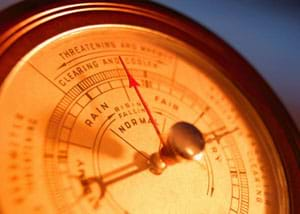 A close-up photograph shows the face of a barometer instrument with an arrow hovering between the markings for Rain and Fair.