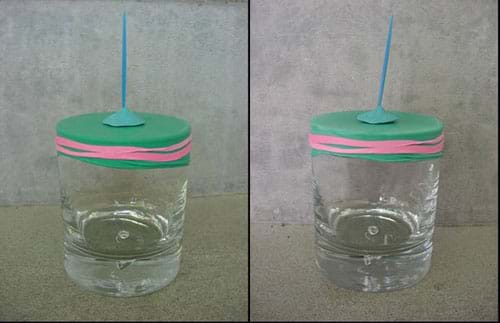 Two photographs both show a glass jar with a rubber band securing a piece of Mylar tight across the jar mouth and a toothpick stuck vertically into a piece of putty on top of the Mylar lid. In the left photo, the toothpick points straight up. In the right photo, the toothpick leans a bit to the right.