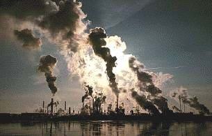 A photograph of a factory releasing air pollutants near a body of water.