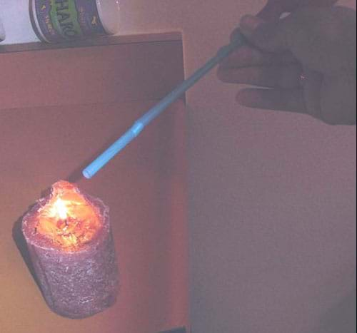 A photograph shows a tilted bottle with a plastic drinking straw attached to its mouth. The other end of the straw is positioned near the flame of a burning candle.