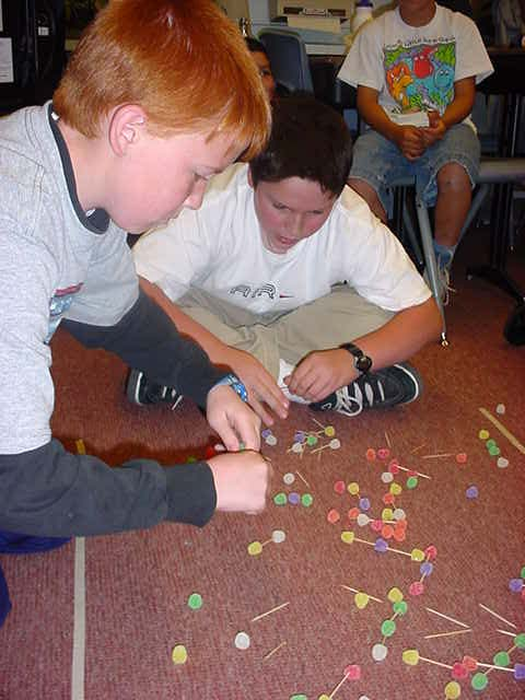 Two students sitting on the floor surrounded by a scattering of toothpicks and gumdrops.