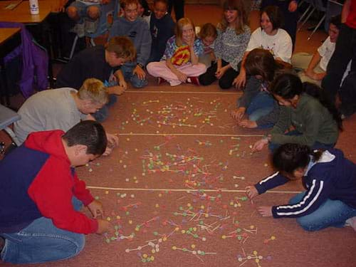 Students cluster around a carpeted area strewn with molecules made from toothpicks and gumdrops.