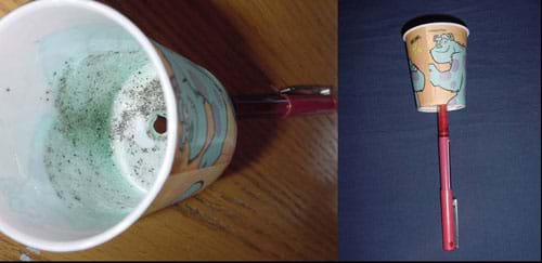 Two photos: 1) Side view of a paper cup with a pen stuck through its base. 2) View of the inside of the cup, with smeared petroleum jelly and black pepper flecks.