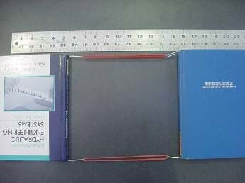 A photo shows two books attached together with a sling-type setup made with rubber bands and paperclips. A ruler is in place to measure the movement of the books before and after the books are pulled apart.