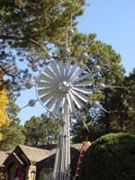 Photo shows a silver windmill-type outdoor kinetic sculpture.