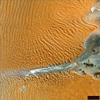 Aerial photo shows waves of orange sand around a river delta.