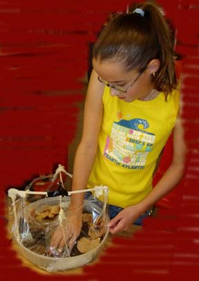 Photo of a girl putting material into the bottom of her plastic model biodome.