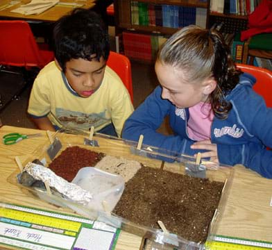 Photo of a two students looking at the sand, soil, bark, and water pool in the base of their model biodome.