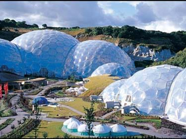 Landscape photo shows cluster of community buildings including geodesic greenhouse domes.