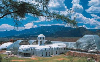 Photo of glass domes and greenhouses with a mountain backdrop.