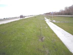 Photo shows a grassy area to the side of a highway, sloping down to a concrete collection drain.
