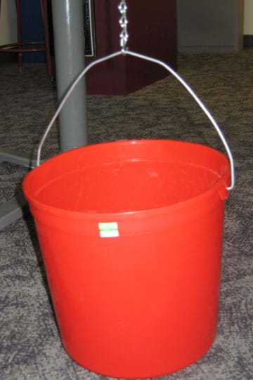 Photo shows the handle of a red bucket held up by an S-hook and chain.