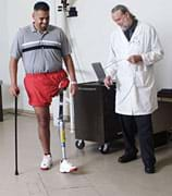Photo shows a man testing his prosthetic leg as a doctor looks on.
