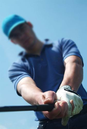 Photo shows golfer using two hands to grip the shaft of a golf club.