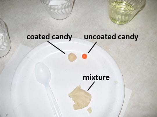 Photo shows a piece of candy covered with the beige mixture (coated) next to a piece of red candy (uncoated) on a paper plate.