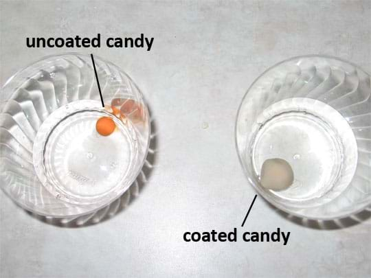 Photo shows an uncoated piece of reddish candy and a whitish coated piece of candy in separate cups of clear soda.