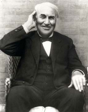 Black and white photo shows a seated and smiling Thomas Edison cupping his right hand around his right ear.