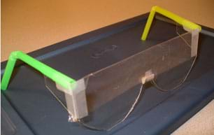 Photo shows rudimentary glasses made with clear cut plastic for lenses, bent straws for temples and tape.