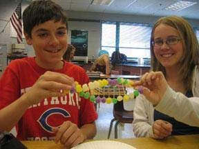 Photo shows two students holding a twisted ladder-like creation made of gumdrops and toothpicks.