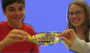 Photo shows two students holding a gumdrop and toothpick creation shaped like a DNA double helix.