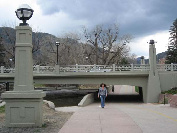 A concrete beam bridge spans a river and a pedestrian path.