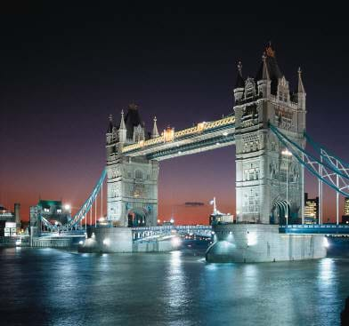 Dusk photo shows lighted two-tower bridge with cables.