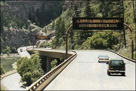 Photo shows a split highway, one route runs low along a river, the other roadway is elevated on columns.